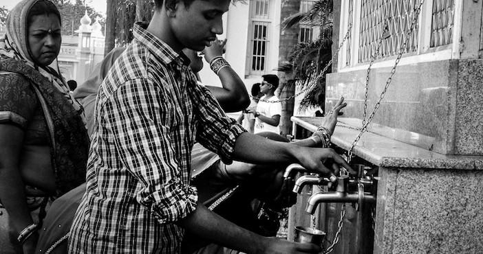 Des Indiens se servent d'eau en libre service dans les rues de Mysore.