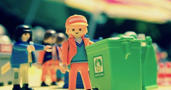Un éboureur playmobil pourrse une poubelle de tri verte.